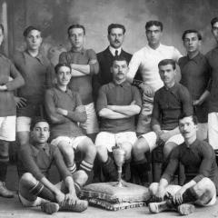 Posant amb el trofeu del Campionat de Catalunya conquistat amb el F.C. España. 1912-1913. Reguera, Bau (dempeus segon per l'esquerra), Olivé, Vernet, Baró, Mariné, Duval, Graells, Passani, Miguel, Ramirez